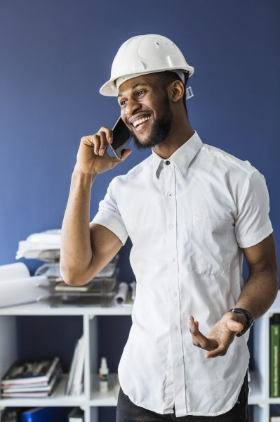 smiling-african-architect-talking-mobile-phone-office